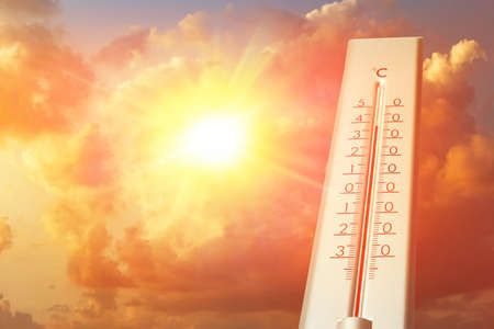 Weather thermometer showing high temperature and sunny sky with clouds on background Imagens
