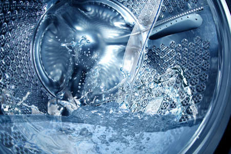 Closeup view on washing machine drum filling with water