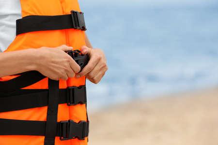 Female lifeguard putting on life vest near sea, closeup Stock Photo