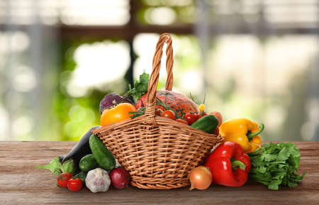 Wicker basket with fresh vegetables on wooden table in kitchen