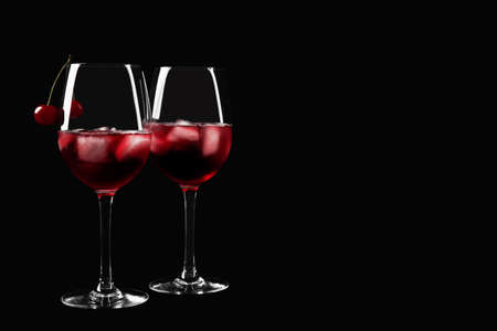 Delicious cherry wine with ripe juicy berries on black background. Space for text
