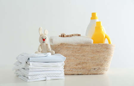 Fresh baby laundry and bottles of detergent on white background