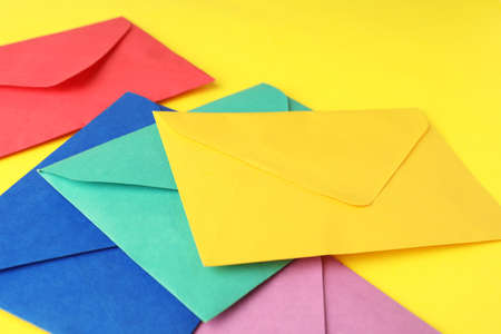 Colorful paper envelopes on yellow background, closeup