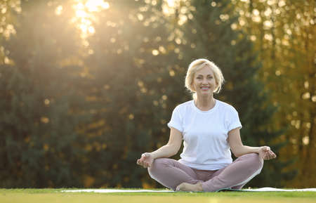 Mature woman practicing yoga on green grass in park Imagens