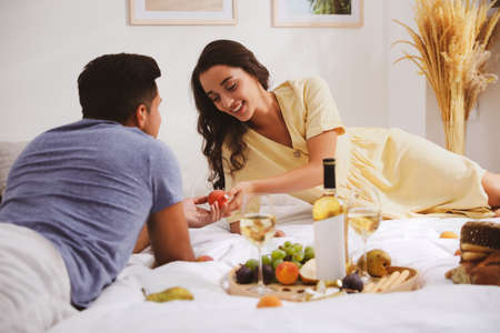Happy couple with wine and tasty food imitating picnic at home