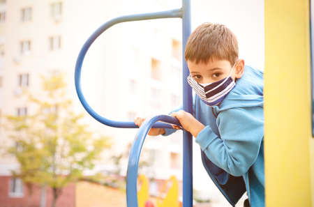 Little boy with medical face mask on playground during covid-19 quarantine Zdjęcie Seryjne