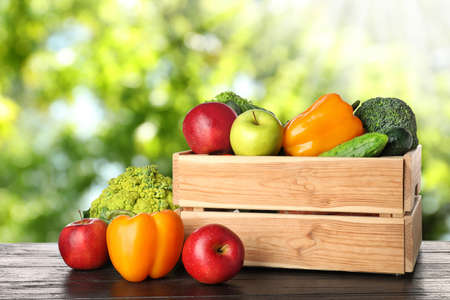Wooden crate with fresh vegetables and fruits on table against blurred background