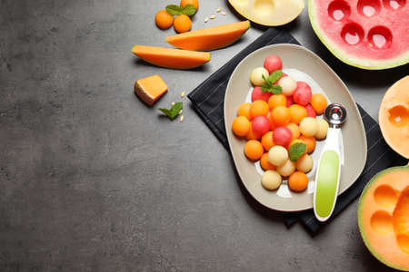 Flat lay composition with melon and watermelon balls on gray table, space for text Stock Photo