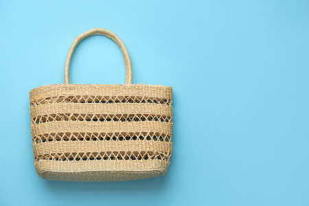 Elegant woman's straw bag on light blue background, top view. Space for text Banque d'images
