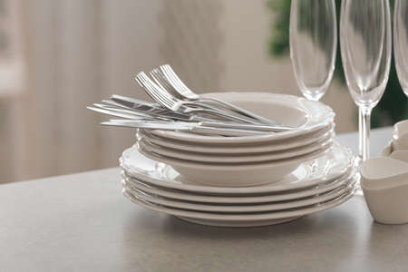 Set of clean dishware, cutlery and champagne glasses on table indoors