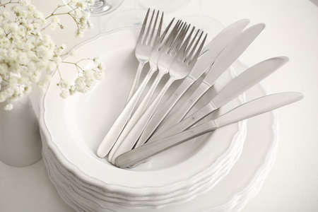 Stacked plates with cutlery on white table, closeup