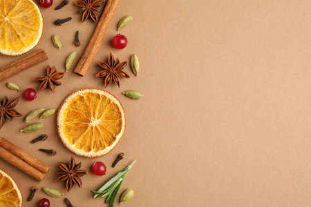 Different mulled wine ingredients on brown background, flat lay. Space for text