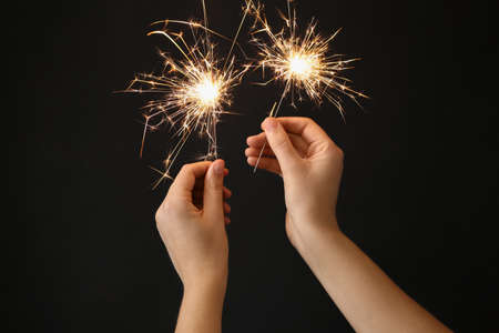 Woman holding bright burning sparklers on black background, closeup Banque d'images