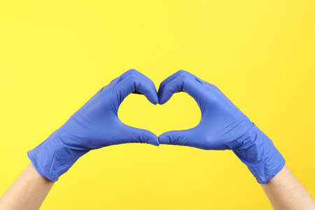 Person in medical gloves showing heart gesture on yellow background, closeup of hands