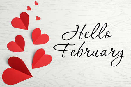 Greeting card with text Hello February. Red paper hearts on white wooden background, flat lay