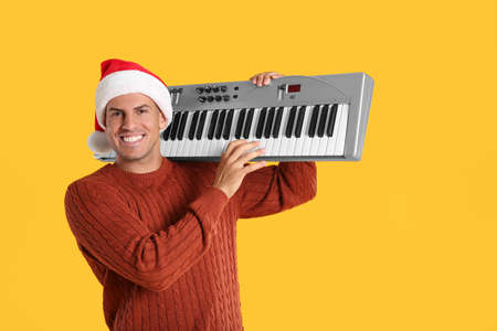 Man in Santa hat playing synthesizer on yellow background. Christmas music Stock Photo