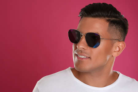 Handsome man wearing sunglasses on pink background, closeup. Space for text