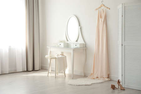 Beautiful wedding gown hanging near dressing table in room Banque d'images