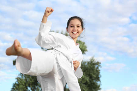 Cute little girl in kimono training karate outdoors
