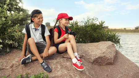 Cute little children with backpacks sitting on rock near river. Camping trip