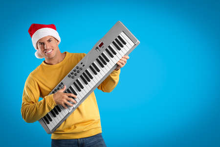 Man in Santa hat playing synthesizer on light blue background, space for text. Christmas music