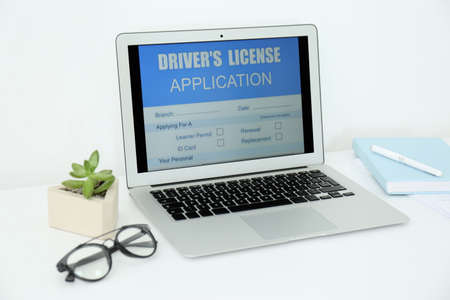 Laptop with driver's license application form on table in office