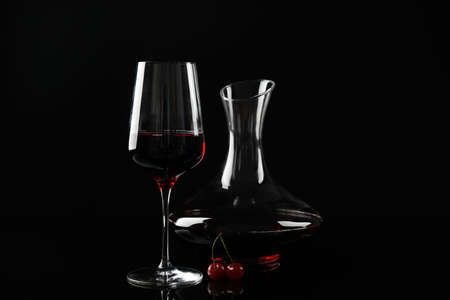 Delicious cherry wine and ripe juicy berries on black background