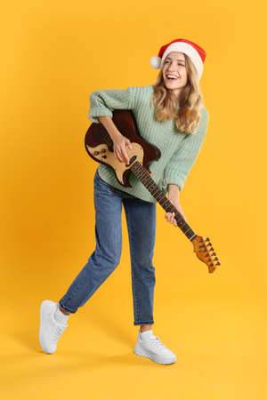 Young woman in Santa hat playing electric guitar on yellow background. Christmas music Foto de archivo - 158336160