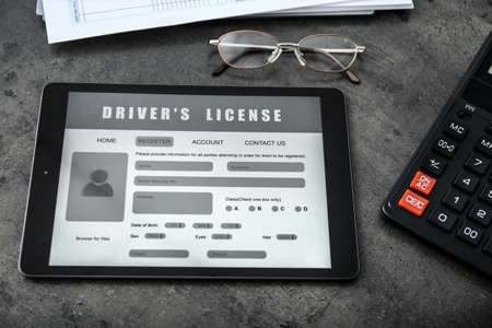 Tablet with driver's license application form, glasses and calculator on gray table
