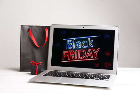 Laptop, shopping bag and gift box on white table. Black Friday Sale online