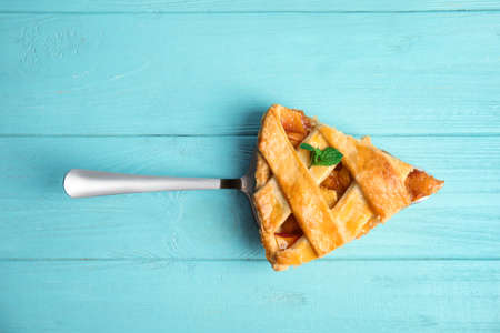 Slice of delicious fresh peach pie on light blue wooden table, top view