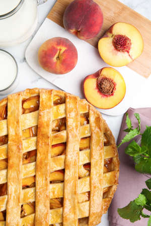 Delicious peach pie and fresh fruits on white marble table, flat lay