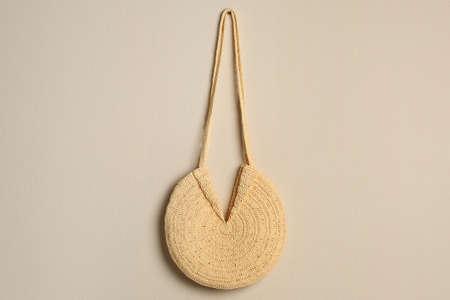Elegant woman's straw bag hanging on beige background