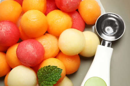 Melon and watermelon balls with scoop on plate, closeup Stock Photo
