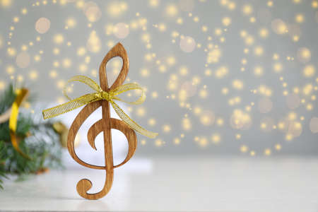 Wooden music note with golden bow on light gray table against blurred Christmas lights. Space for text