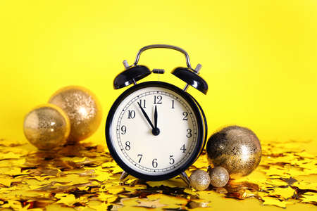 Vintage alarm clock with Christmas decor on yellow background. New year countdown