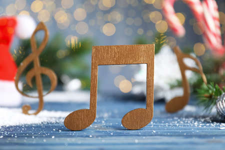 Wooden music note on light blue table against blurred Christmas lights Stock Photo