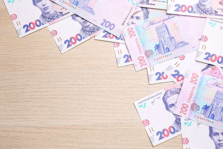 Ukrainian money on wooden background, flat lay. Space for text