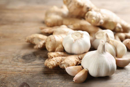 Ginger and fresh garlic on wooden table, closeup. Natural cold remedies