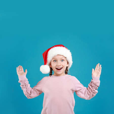 Excited little child in Santa hat on light blue background. Christmas celebration
