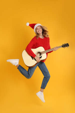 Young woman in Santa hat jumping with acoustic guitar on yellow background. Christmas music Stock Photo