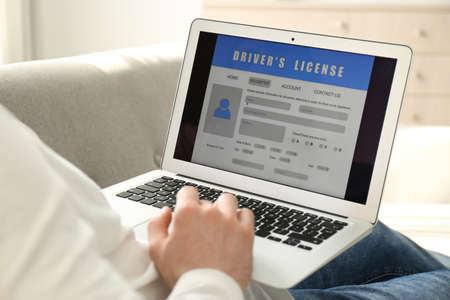 Man using laptop to fill driver's license application form at home, closeup