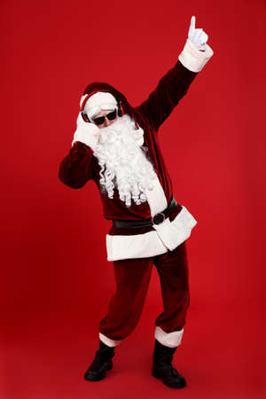 Santa Claus with headphones listening to Christmas music on red background