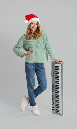 Young woman in Santa hat with synthesizer on light gray background. Christmas music