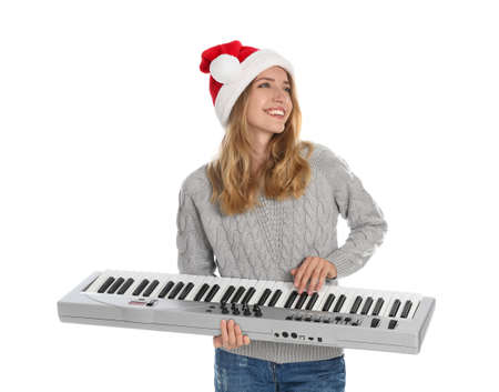 Young woman in Santa hat playing synthesizer on white background. Christmas music