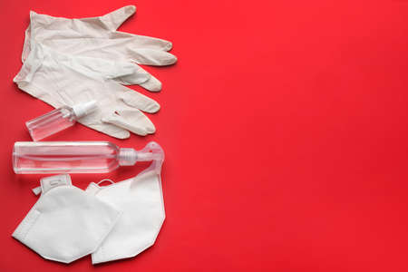 Flat lay composition with medical gloves, masks and hand sanitizers on red background. Space for text