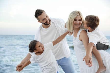 Happy family having fun on beach near sea Standard-Bild