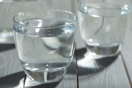Glass of water on gray wooden table, closeup. Refreshing drink