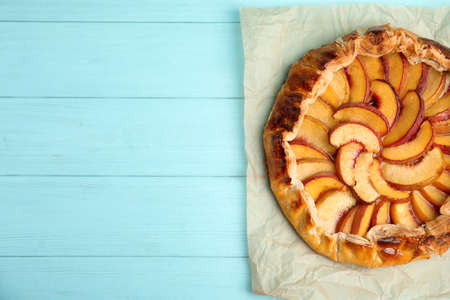 Delicious fresh peach pie on light blue wooden table, top view. Space for text 版權商用圖片