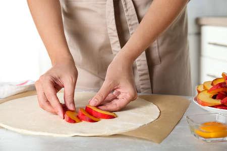 Woman making peach pie at kitchen table, closeup